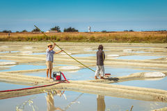 Two men harvest salt in the traditional way in the salt marshes Stock Photo