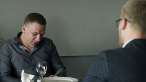 Two men have lunch speak in break up sitting at cafe indoors. Brown-haired man in grey shirt speaking with colleague, telling story, waiting for order. Blonde stock footage