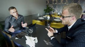 Two men have lunch speak in break up sitting at cafe indoors.  stock video