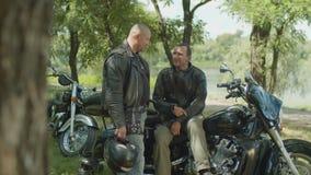 Two men having a break after motorbike ride stock video