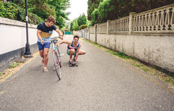 Two men having fun riding bike and skateboard. Two men laughing and having fun riding bike and skateboard in the street on a sunny day. Young lifestyle concept Royalty Free Stock Images