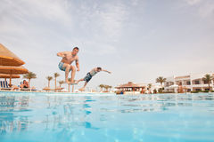Two men having fun at swimming pool. Royalty Free Stock Image