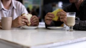 Two men having lunch in a restaurant. Business lunch. Two men eating sandwiches stock footage