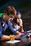 Two men having whiskey and using digital tablet at bar counter Stock Photos