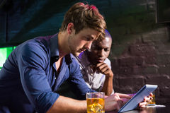 Two men having whiskey and using digital tablet at bar counter Stock Photo