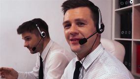 Two men with headsets talking on voice call centre. Businessman turn his head to the camera and smiling. He look very happy of his job. Super slow motion shot stock video footage