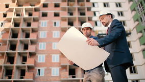 Two men in helmet look at the plan of the house. The man are talking and look around the building stock video footage