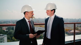 Two men in helmet talk at the roof. Two men in helmet are talking at the roof. The men hold a documents in the hand stock footage