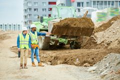 Building inspectors watching excavation process stock images