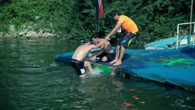 Two men helping swimmers to geting them out. LOGARSKA, SLOVENIA - JUL 20: Two men helping swimmers to geting them out. Championship competition in triatlon in stock video