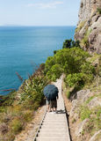 Two men hike The Mount at Tauranga in NZ Stock Photo