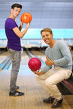 Two men hold balls in bowling club Stock Photo