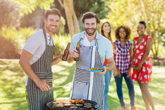 Two men holding a beer bottle while preparing barbecue grill. In park and friends in background Stock Photos