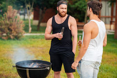 Two men holding a beer bottle while preparing barbecue Royalty Free Stock Image