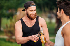Two men holding a beer bottles Stock Photo