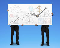 Two men holding board with business doodles and clock hands Royalty Free Stock Photo