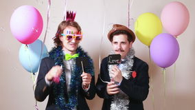 Two men holding boards in love in photo booth stock footage