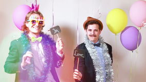 Two men holding boards in love in photo booth stock video