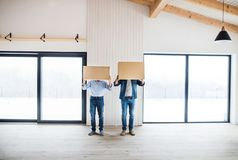 Two men holding cardboard boxes in front of their head when furnishing new house. Two men holding cardboard boxes in front of their head when furnishing new royalty free stock image