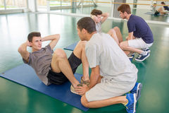 Two men holding feet friends doing situps. Two men holding feet of friends doing situps Royalty Free Stock Image