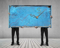 Two men holding old blue doodles billboard on wooden floor Royalty Free Stock Image