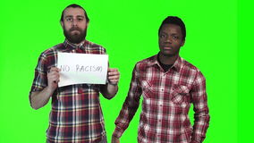 Two men holding up No Racism sign. Two multiracial men eating french fries, one a bearded Caucasian and the other a young black guy, holding up No racism sign stock footage