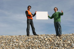 Two Men holding a white card. Two Young Men holding a blank white card at the beach stock photos