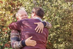 Two men hugging in autumn park royalty free stock photography