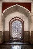 Two Men In Humayan`s Tomb. DELHI, INDIA - NOVEMBER 20, 2016: Two men frame a window inside Humayan`s Tomb in Delhi, India which is richly decorated with inlaid royalty free stock photo
