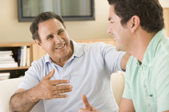 Free Two Men In Living Room Talking And Smiling Royalty Free Stock Photography - 5548997