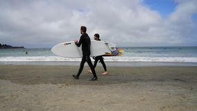 Two Men In Wetsuits Carrying Surfboards, Walking Along Sandy Shore Of The Pacific Ocean Royalty Free Stock Image