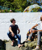 Two men intrigued by a bubble on Portmeirion beach Stock Photos