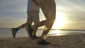 Two Men Jogging on the Beach. Low-angle steadicam shot of two men jogging on the beach, their legs are in shot stock footage