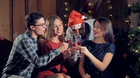 Two men join two women sitting near a Christmas tree. Two men join two women sitting near a Christmas tree to make a toast stock video
