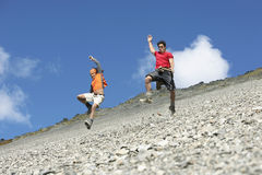 Two Men Jumping Down Scree Field Royalty Free Stock Images