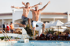 Two men jumping in swimming pool Stock Photo