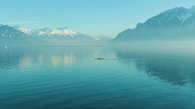 Two Men Kayaking on Clear Day on Blue Lake Geneva. Swiss Alps, Switzerland. Two Men Kayaking on Clear Day on Turquoise Lake Geneva. Snow-Capped Mountains stock video
