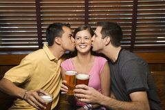 Two men kissing woman. Two men kissing woman in the middle while holding their beers at pub Royalty Free Stock Photos