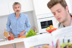 Two men in kitchen one preparing vegetables other reading from recipe book. Man royalty free stock photos
