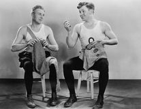 Two men knitting and sewing Stock Images