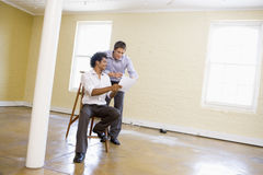 Two men with ladder in empty space Stock Images