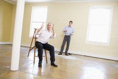 Two men with ladder in empty space Royalty Free Stock Image