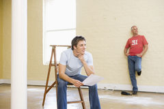 Two men with ladder in empty space Stock Photos