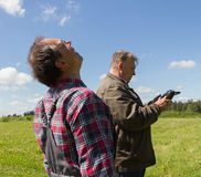 Two men launch drone. Two adult men launch drone on open field Stock Photos
