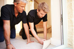 Two men laying underlay for flooring in a house Royalty Free Stock Photo