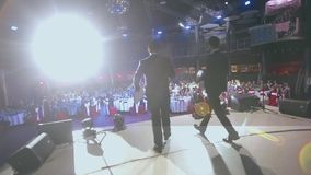 The two men leading go on stage, start to exercise.  stock footage