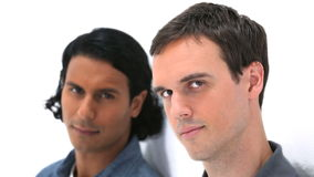 Two men leaning against a wall Stock Photo