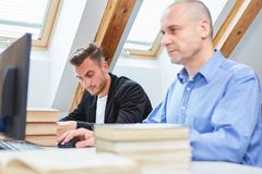 Two men learn at the computer in the training. Two men study on the computer or write an exam in the training royalty free stock image