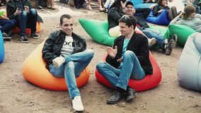 Two men lie on big beanbags on sand. Summer festival. Sunny day. Finger up, clap. Audience stock footage
