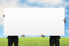 Two men lifting blank board outdoor Stock Images